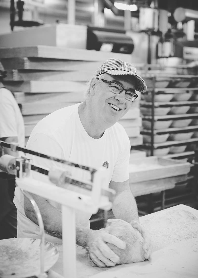 Freundliches Porträt eines Bäckers beim Kneten von Broten mit der Hand Foodreportage und Editorial Bäckerei Geisen Der Brotbäcker