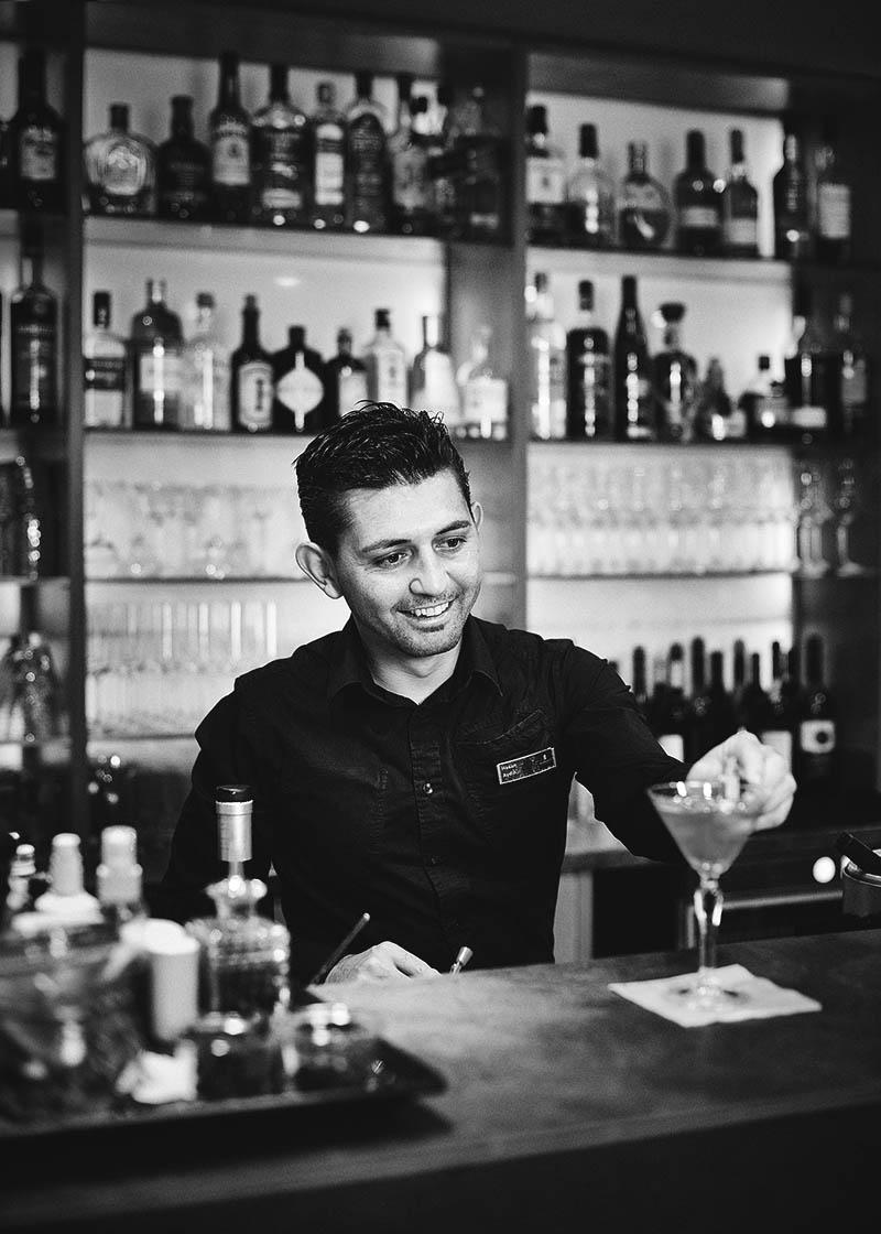 Portraitfoto Barkeeper im Cube bei der Arbeit Hotelfotografie - Imagefotografie und Storytelling für Unternehmen