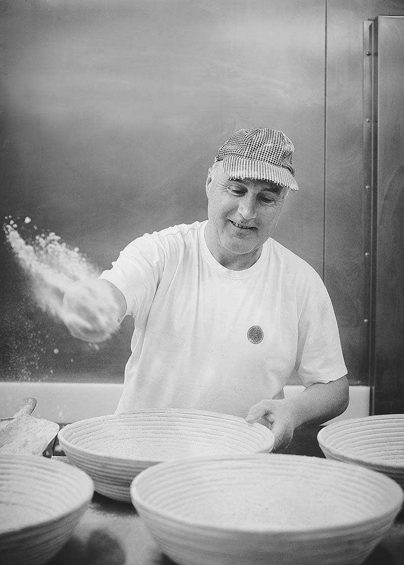 Portraitfoto eines Bäckers beim Mehlen der Brotformen Foodreportage und Editorial Bäckerei Geisen Der Brotbäcker