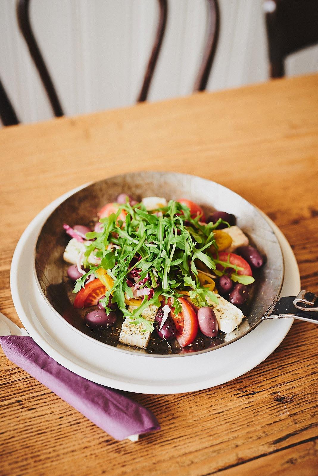 Griechischer Salat mit Feta und Oliven in einer Pfanne angerichtet im Cafe Pfefferminzje in Koblenz - Foodfotografie von Anna Schneider neon fotografie