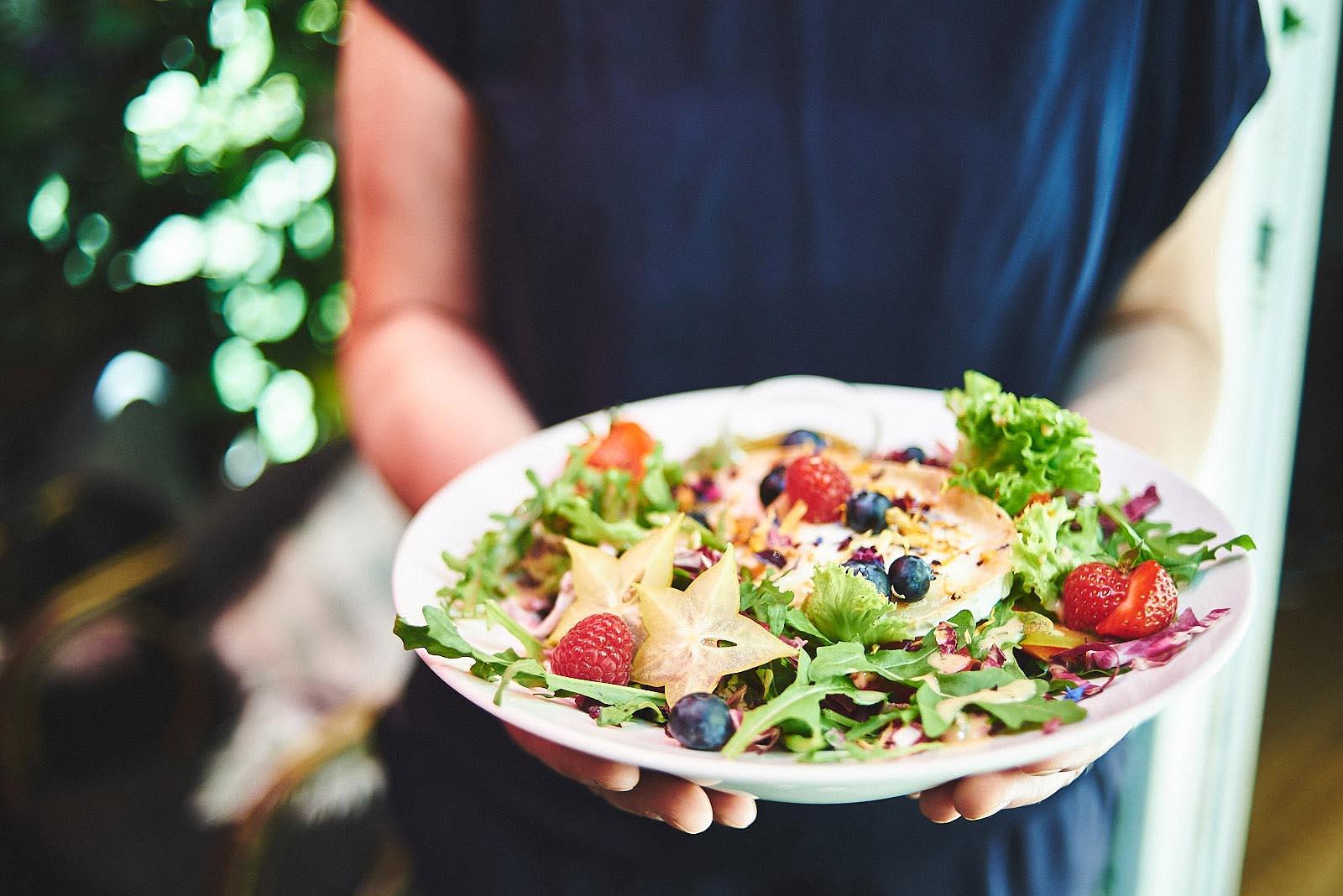 Kellnerin hält liebevoll angerichteten Salat mit Ziegenkäse im Cafe Pfefferminzje in Koblenz in den Händen - Foodfotografie von Anna Schneider neon fotografie