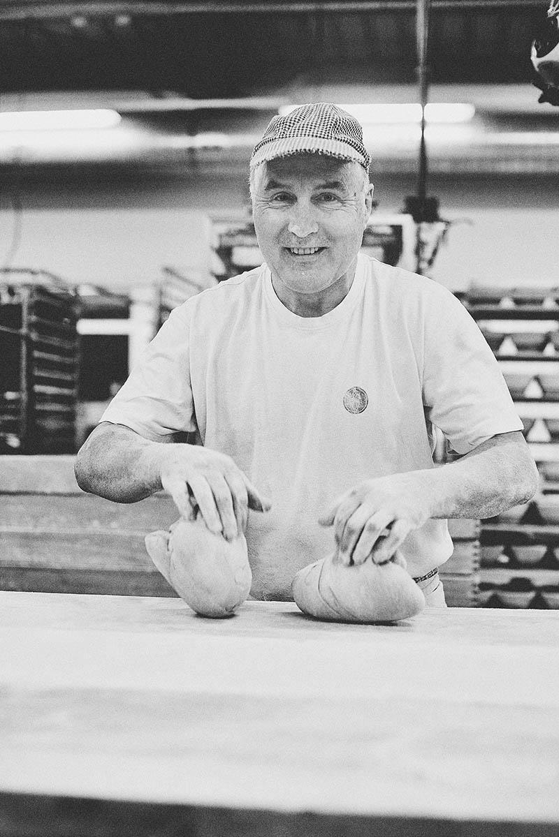 Porträt Bäcker beim beidhändigen Kneten von Broten Foodreportage und Editorial Bäckerei Geisen Der Brotbäcker
