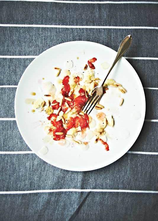 Food-Aufnahme von einem leckeren Erdbeer-Spargel-Carpacchio tabletop auf gestreifter Tischdecke
