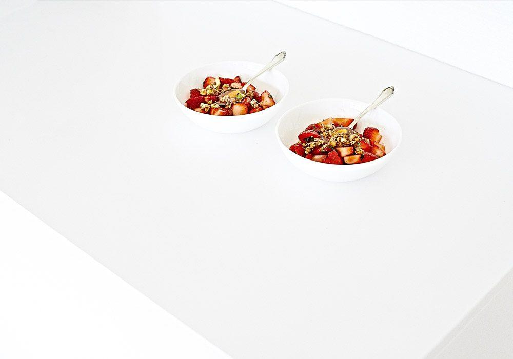 Moderne Food-Fotografie leckeres Dessert mit frischen Erdbeeren und karamellisierten Nüssen in weißer Küche mit viel Freiraum
