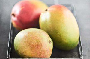 Closeup von reifen Mango Früchten in einem Drahtkorb auf Beton, soft Focus mit viel Unschärfe und Freiraum   Moderne Foodfotografie - neon fotografie