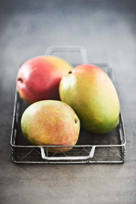 Closeup von reifen Mango Früchten in einem Drahtkorb auf Beton, soft Focus mit viel Unschärfe und Freiraum | Moderne Foodfotografie - neon fotografie