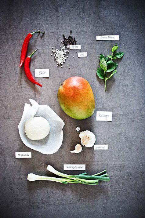 Zutaten für einen Salat mit Mango, Mozarella, Chilli und Minze tabletop fotografiert auf Beton beschriftet mit kleinen Kärtchen | Modernen Foodfotografie - neon fotografie