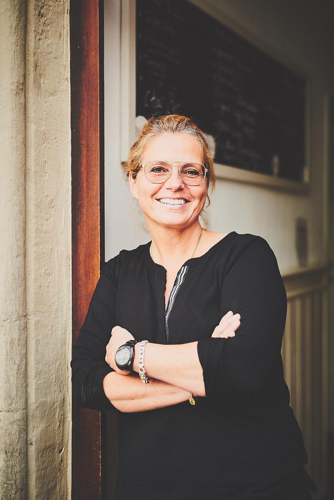 Portraitfoto Nicole König im Eingang des Cafe Pfefferminzje in Koblenz - Porträtfoto von Anna Schneider neon fotografie