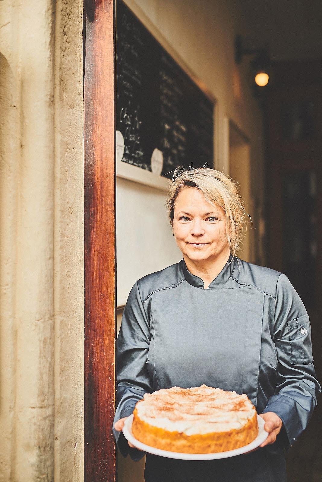 Porträt-Foto Konditorin im Cafe Pfefferminzje in Koblenz mit frisch gebackenem Kuchen in der Hand - moderne Portrait-Fotografie von Anna Schneider neon fotografie