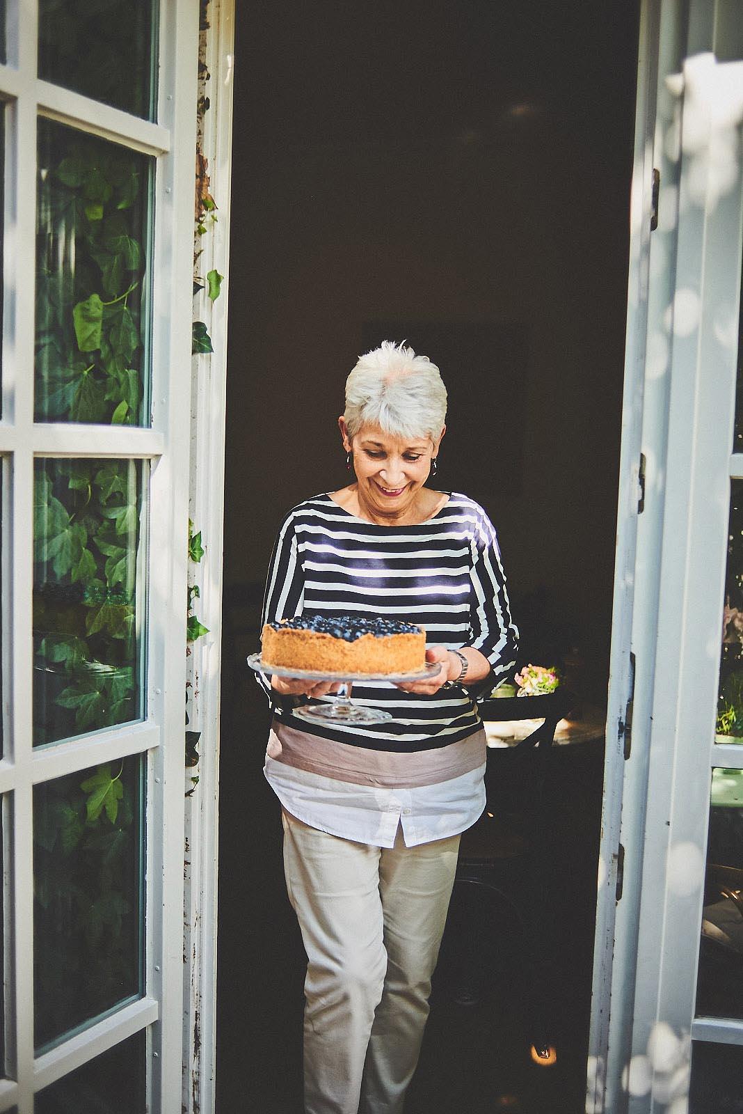 Dame bringt frisch gebackenen Heidelbeerkuchen zu den Gästen im Cafe Pfefferminzje in Koblenz - Portraitfoto von Anna Schneider neon fotografie