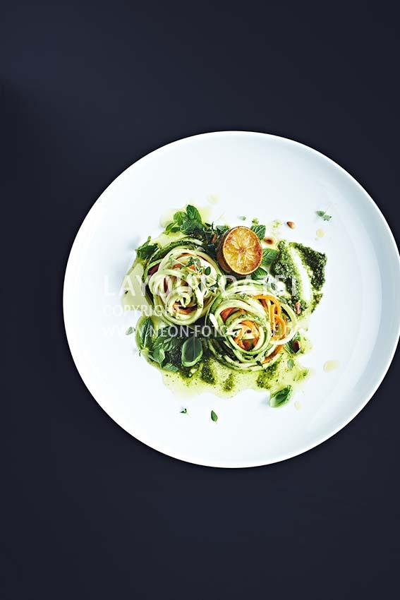 Food-Fotografie vegetarische Gemüse-Spaghetti aus Zucchini und Möhren mit Limetten und grünem Basilikum-Pesto Stock