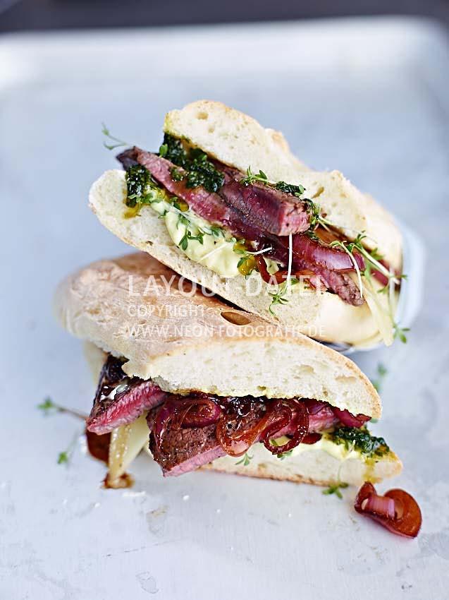 Leckeres Steak-Sandwich mit Balsamico-Zwiebeln und Pesto - moderne Food-Fotografie