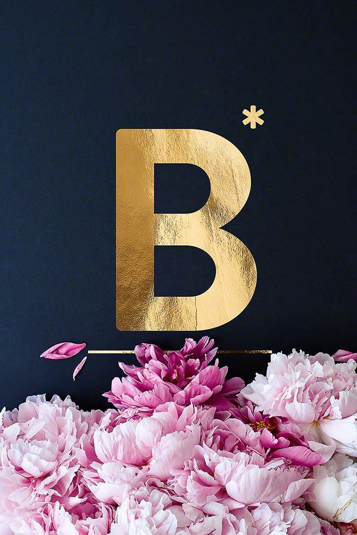 B - Goldenes Alphabet auf schwarzem Hintergrund mit Pfingstrosen