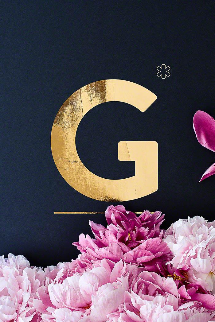 G - Goldenes Alphabet auf schwarzem Hintergrund mit Pfingstrosen