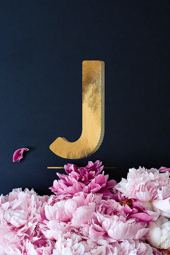 J - Goldenes Alphabet auf schwarzem Hintergrund mit Pfingstrosen