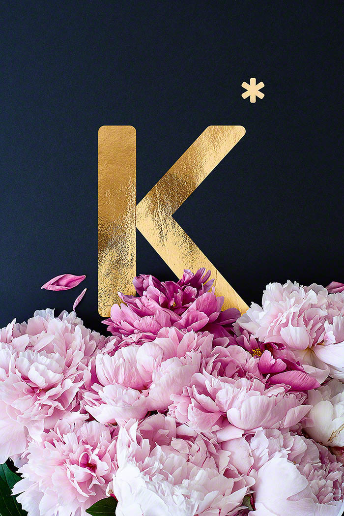 K - Goldenes Alphabet auf schwarzem Hintergrund mit Pfingstrosen