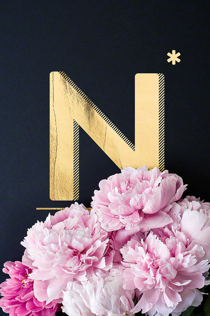 N - Goldenes Alphabet auf schwarzem Hintergrund mit Pfingstrosen