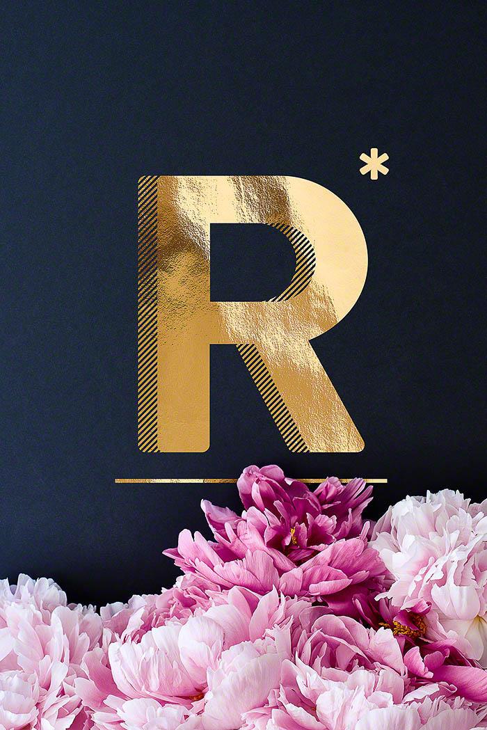 R - Goldenes Alphabet auf schwarzem Hintergrund mit Pfingstrosen