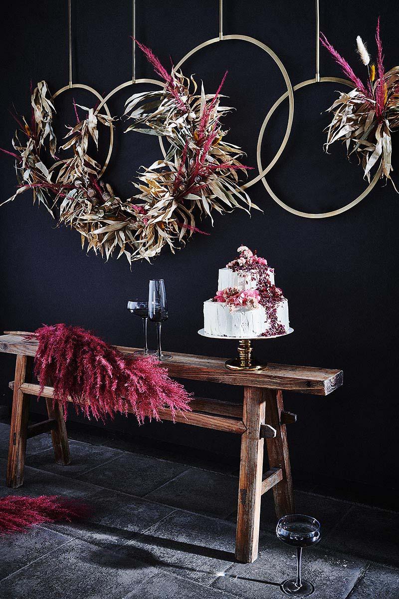 Hochzeitstorte mit Blüten und Himbeeren + Dekoelement aus Ringen und Bambus